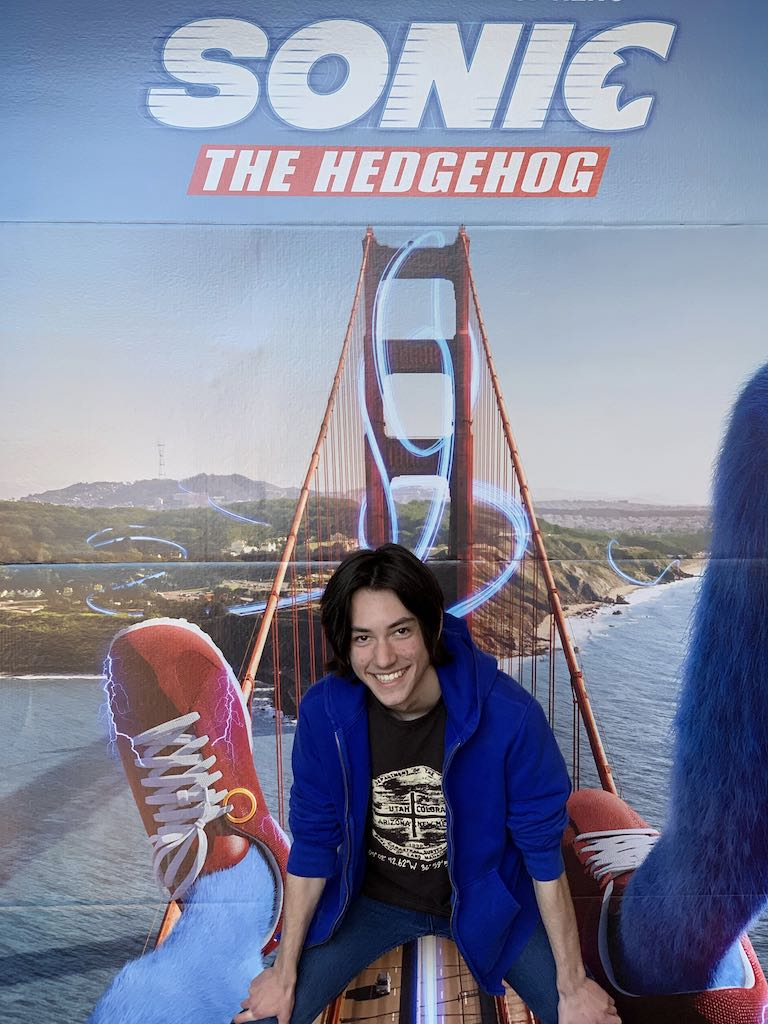 Augie poses in front of the somewhat perverted poster for the Sonic the Hedgehog movie